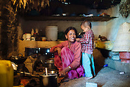 Rama Shrestha, 29, plays with her son as she cooks breakfast inside her one-room house. Shrestha and her husband both work at the nearby brick kiln outside of Kathmandu, Nepal.