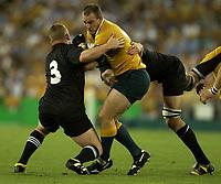 Photo: Richard Lane.<br />New Zealand v Australia. Semi-Final, at the Telstra Stadium, Sydney. RWC 2003. 15/11/2003. <br />Stirling Mortlock is tackled by Greg Somerville and Chris Jack.