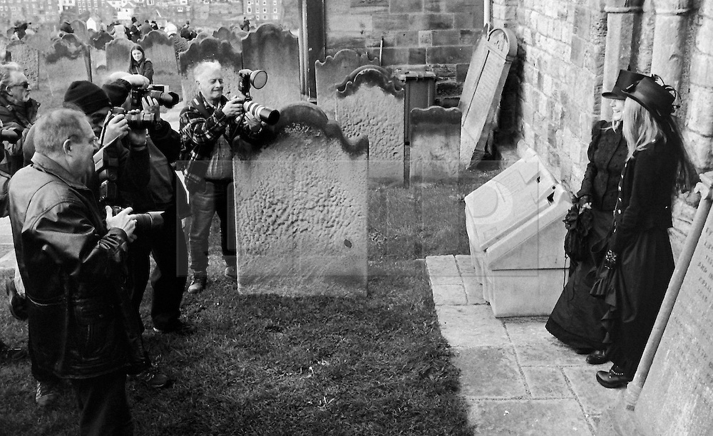 © Licensed to London News Pictures.01/11/15<br /> Whitby, UK. <br /> <br /> Two women wearing gothic clothing pose as amateur photographers take their picture as hundreds of visitors attend the Whitby Goth weekend in Whitby, North Yorkshire. The event began in 1994 to celebrate goth culture and music and takes place twice each year. <br /> Thousands of extravagantly dressed people attend the popular event wearing Steampunk, Cybergoth, Romanticism, Victoriana and other clothing as they take part in the celebration of Goth culture. <br /> <br /> Note to Editors - Picture shot on Kodak Tri X 400ISO film.<br /> Photo credit : Ian Forsyth/LNP