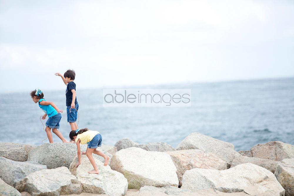 Children Climbing on Rocks by Sea