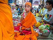 """06 APRIL 2015 - CHIANG MAI, CHIANG MAI, THAILAND: Boys put their monks' robes on for the first time during their ordination on the last day of the three day long Poi Song Long Festival in Chiang Mai. The Poi Sang Long Festival (also called Poy Sang Long) is an ordination ceremony for Tai (also and commonly called Shan, though they prefer Tai) boys in the Shan State of Myanmar (Burma) and in Shan communities in western Thailand. Most Tai boys go into the monastery as novice monks at some point between the ages of seven and fourteen. This year seven boys were ordained at the Poi Sang Long ceremony at Wat Pa Pao in Chiang Mai. Poy Song Long is Tai (Shan) for """"Festival of the Jewel (or Crystal) Sons.   PHOTO BY JACK KURTZ"""