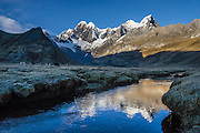 """At sunrise, donkeys graze by a stream flowing through Tuctucpampa campground below Nevado Jirishanca (left, """"Icy Beak of the Hummingbird"""" 6094 m) and Rondoy (right 5870 m). Day 2 of 9 days trekking around the Cordillera Huayhuash, in the Andes Mountains, Peru, South America."""