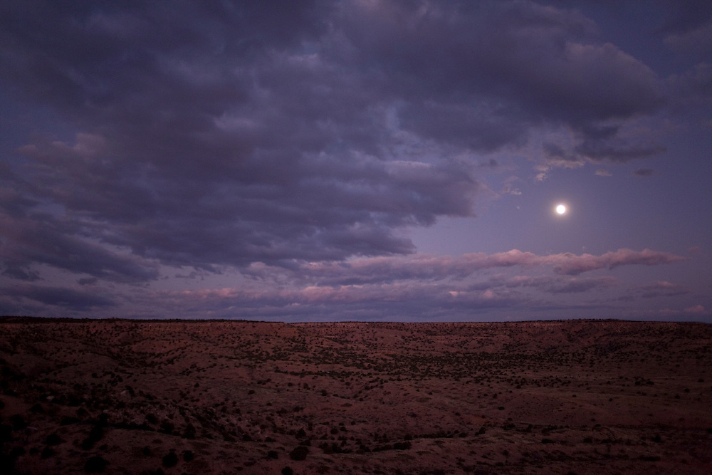 The Harvest Moon sets behind the Honanie home on Third Mesa.