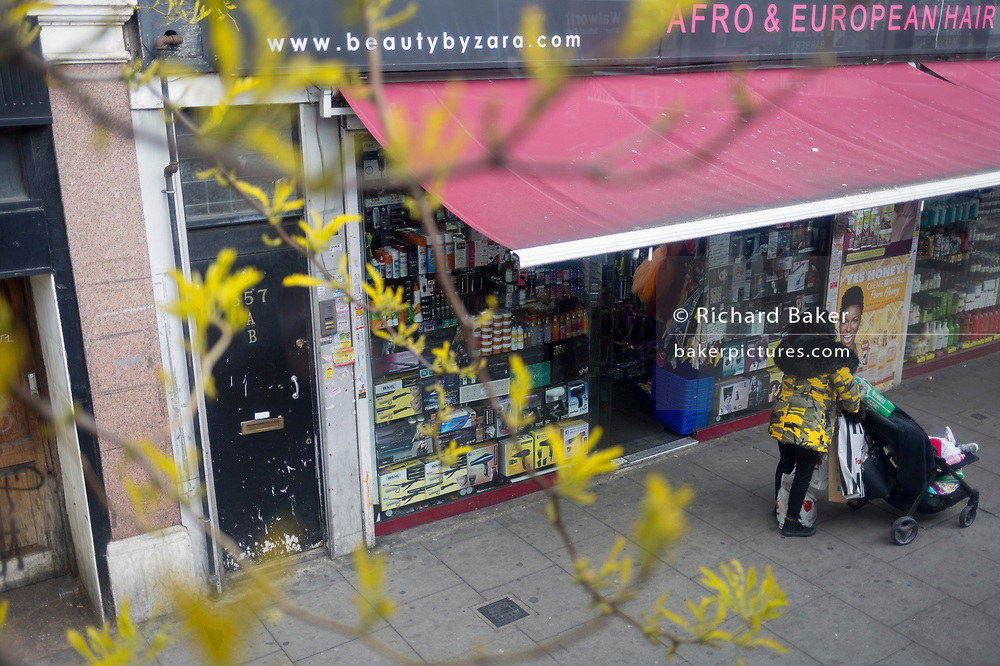 The yellow shoots from an urban tree growing near a Cashino on the Walworth Road in Southwark, on 29th April 2019, in London, England.