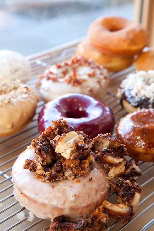 Bluestar Donuts featuring, Fried Chicken over original glazed (front center) - Chocoalate Cocnut Ganache -Creme Brûlée w/ vanilla custard - Blueberry, Bourbon, Basil - Meyer Lemon & key lime curd - Real Maple and bacon - original glazed -