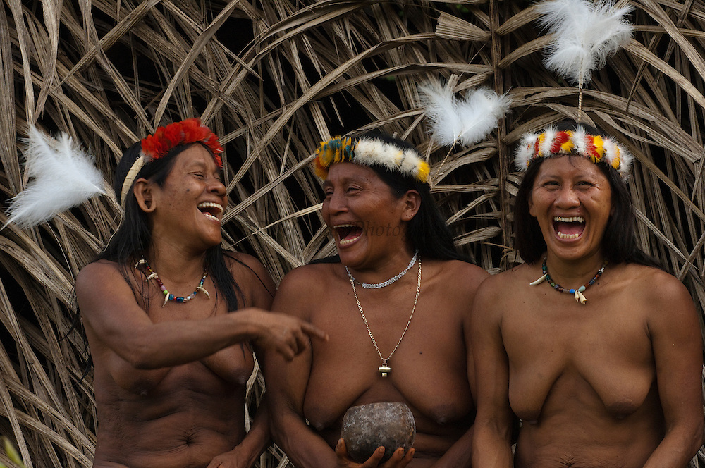 Huaorani women, Awame Gomoke & Dete Iteka & Ewa Kemperi all wearing crowns topped with Harpy Eagle feather. They are also sharing Chicha drink from a home made pottery bowl.<br /> Bameno Community. Yasuni National Park.<br /> Amazon rainforest, ECUADOR.  South America<br /> This Indian tribe were basically uncontacted until 1956 when missionaries from the Summer Institute of Linguistics made contact with them. However there are still some groups from the tribe that remain uncontacted.  They are known as the Tagaeri & Taromenane. Traditionally these Indians were very hostile and killed many people who tried to enter into their territory. Their territory is in the Yasuni National Park which is now also being exploited for oil.