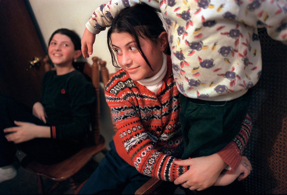 Leonora, Saliu  left, laughs as Alma Saliu, right, gives her brother Urim a hug at home in their St. Paul home. The twins, 11, take charge and care for their younger siblings when their parents are away. Forced to flee from their Kosovo home  during the ethnic cleansing campaign by the Serbs , the Albanian family relocated to the Twin Cites and are struggling to adjust.