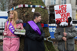 London, UK. 12th January, 2018. Anne Stevens (c), the vicar of St Pancras church, stands chained with local resident Jo Hurford (l) to a tree outside Euston station during a protest against the HS2 high-speed rail link. The protest formed part of a campaign by local residents against the planned felling of mature London Plane, Red Oak, Common Whitebeam, Common Lime and Wild Service trees in Euston Square Gardens to make way for temporary HS2 sites for construction vehicles and a displaced taxi rank.