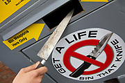 A knife being put inside a Knife bin, ouside St Iganatius church, Seven Sisters, London.