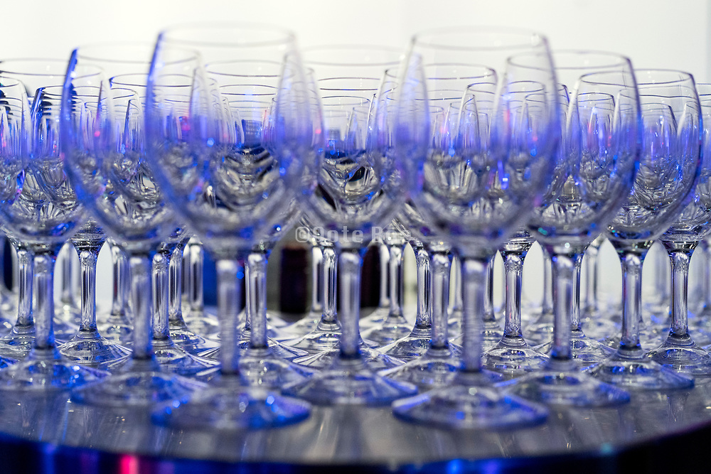 many empty wine glasses standing on a bar counter