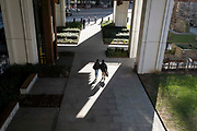 While office workers remain at home in accordance to government Covid guidelines and individual corporate policies, some Londoners walk in warm spring sunshine beneath Bassishaw Highwalk in the City of London, the capitals financial district, during the third lockdown of the Coronavirus pandemic, on 9th March 2021, in London, England.