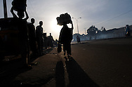 Pedestrians and street vendors move along a busy street in Kano, Nigeria on Thursday evening, December 6, 2012.