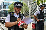 A member of MET Police writes on his workbook during a Police lockdown of the Home Office in Marsham Street after a victim staggered into the Home Office reception looking for help after being stabbed in the street in central London on Thursday, 15 Aug 2019. (Photo/Vudi Xhymshiti)