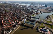 Nederland, Zuid-Holland, Capelle aan den IJssel, 20-03-2009; stormvloedkering in de Hollandsche IJssel. Bij storm en dreigend hoog water wordt een van de twee schuiven naar beneden gelaten, de tweede schuif dient al reserve. De scheepvaart kan de gesloten kering paseren via de naastgelegen schutsluis. Links Krimpen aan den IJssel, boven in beeld de Nieuwe Maas en Rotterdam (Bolnes).   .De stormvloedkering maakt deel uit van de Deltawerken en is als eerste voltooid in 1958. Ten tijde van De Ramp - watersnood 1953 - werd het zeewater door de storm opgestuwd en dreigde de verzwakte rivierdijken in het achterland het te begeven waardoor grote van het laag gelegen westen van Nederland ondergelopen zouden zijn..Netherlands, Capelle at the river IJssel, near Rotterdam: storm surge barrier, protects the highly populated western part of Holland, which lies below sea level. In case of storm and threat of high water, one of the two doors is lowered into the river (the second door is a spare one). The lock next to the barrier allows shipping when the barrier is closed.Swart collectie, luchtfoto (toeslag); Swart Collection, aerial photo (additional fee required).foto Siebe Swart / photo Siebe Swart