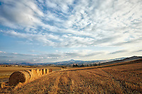 A golden field and hay bales in Val d'Orcia in Tuscany, Italy.