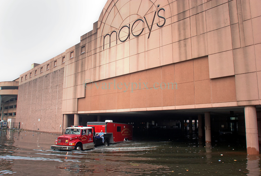 30 August 2005. New Orleans, Louisiana. <br /> Hurricane Katrina aftermath. <br /> A fire truck passes below the flooded Macy's in New Orleans.<br /> Photo Credit: Charlie Varley/varleypix.com