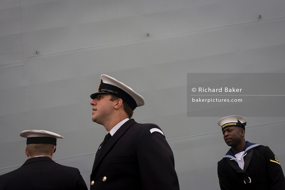 Student officers and a sailor rating on duty beneath the giant hull of their ship during a tour by the general public on-board the Royal Navy's aircraft carrier HMS Illustrious during a public open-day in Greenwich. Illustrious docked on the river Thames, allowing the tax-paying public to tour its decks before its forthcoming decommisioning. Navy personnel helped with the PR event over the May weekend, historically the home of Britain's naval fleet.