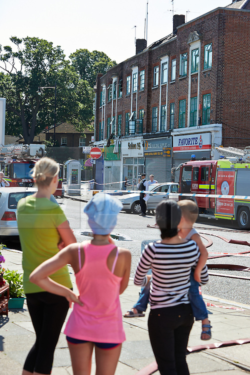 © Licensed to London News Pictures.  10/07/2013. LONDON, UK. Local residents look towards the scene of a fatal fire in flat above a shop on New Heston Road (Church Road), Hounslow. Two men and a woman jumped from the building before fire crews arrived. The woman, thought to be 30 years old, died at the scene and another body was discovered inside. Photo credit: Cliff Hide/LNP