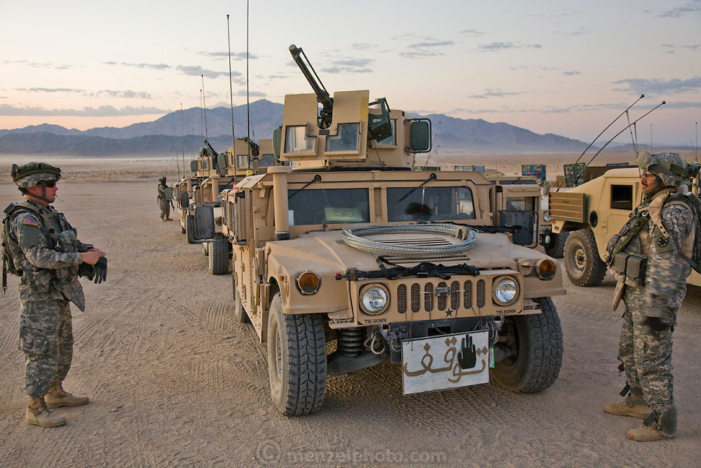 Military vehicles with Arabic calligraphy used for training soldiers during simulated combat conditions before deploying to Iraq at Medina Jabal, an Iraqi town at Fort Irwin, California.