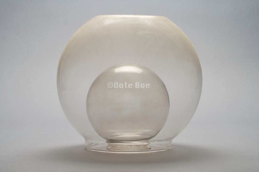 two glass bolls of which the outer one is covered with dust