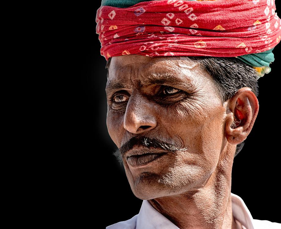 Headshot portrait of man wearing a red turban