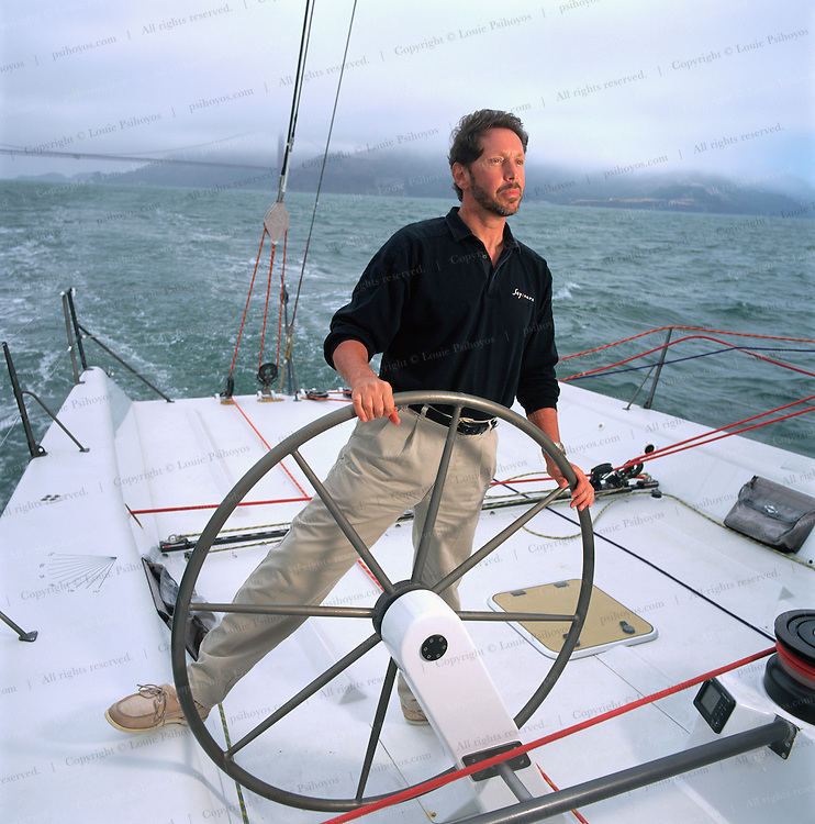 Larry Ellison, software billionaire and CEO of Oracle Corporation at the helm of his sailing yacht Sayonara San Francisco Bay.