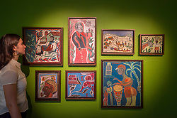 """© Licensed to London News Pictures. 02/10/2018. LONDON, UK. A staff member poses in a room full of Haitian paintings. Preview of """"Art + Revolution in Haiti"""", an exhibition at The Gallery of Everything in Chiltern Street.  The exhibition, which coincides with Frieze Week, explores when Surrealism arrived in the former slave colony in 1945.  Works from artists from le Centre d'Art d'Haiti and from the personal collection of Andre Breton, the founder of Surrealism, are on display until 11 November 2018.  Photo credit: Stephen Chung/LNP"""