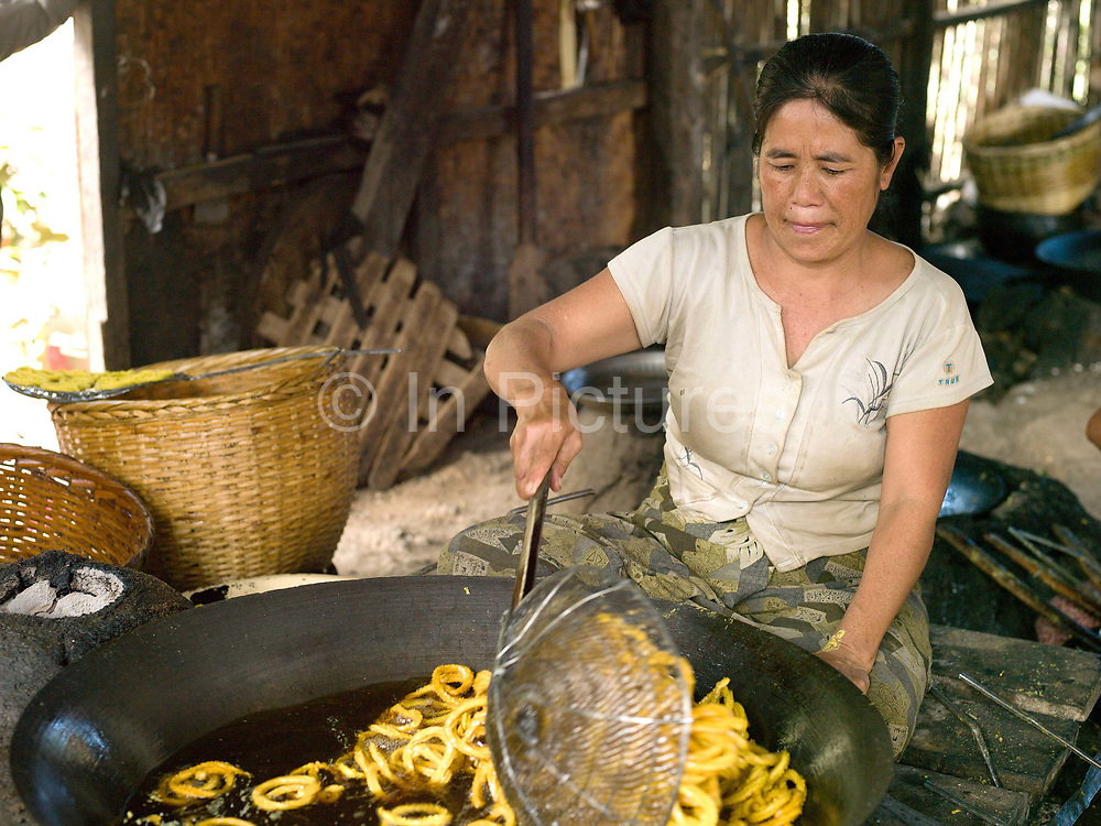 An Intha woman cooks snacks in boiling oil, Kaung Daing village on the shore of Inle lake, Shan State, Myanmar (Burma).