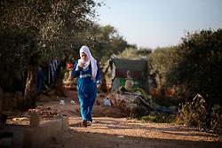 A Syrian refugee walks through the settlement camp where she lives amongst an olive grove in Koura, near Tripoli, Lebanon.