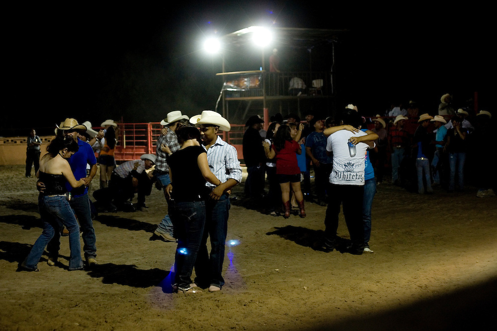 Julia Robinson photo.A young couple dances to live music in the arena at the end of a jaripeo at El Bajio in Von Ormy, Texas.  Live music is a popular addition to the charreada and draws crowds after the sun goes down.