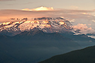 Mount Rainier evening alpenglow lights the volcano in warm light with bands of clouds and summit clouds viewed from the Mount Tahoma Trails Association's High Hut in the Tahoma State Forest, WA, USA