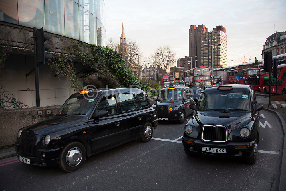 Black taxi drivers protest against taxi service app Uber, blocking Waterloo. Joined in many numbers by future black cab drivers on mopeds currently doing The Knowledge. London cabbies emphasised that they had no problem with Uber, only with Transport for London for not enforcing current legislation. Taxi drivers say the Uber app is tantamount to a meter and should be regulated like taxi meters. Uber says it has seen an 850% increase in sign-ups compared to last Wednesday and describes the London Taxi Drivers Association LTDA, as being stuck in the dark ages.London, England, United Kingdom.