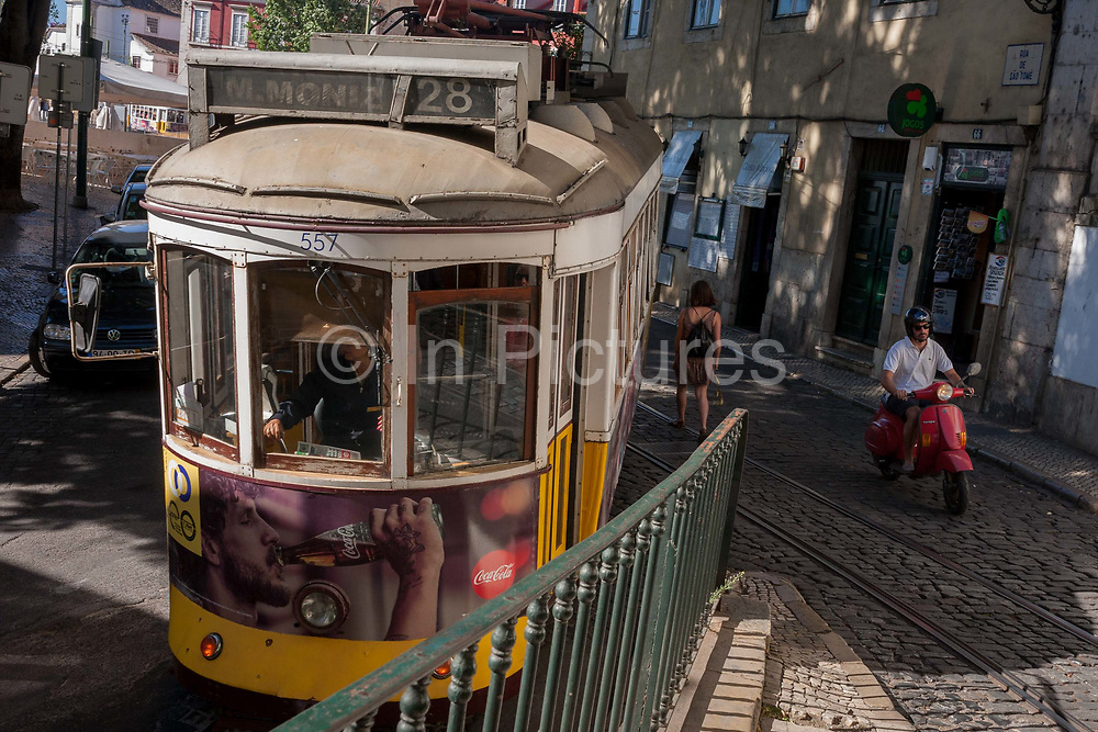 As a scooter rider on a Vespa edges past, a number 28 tram rumbles along a narrow street in the Portuguese capital, on 13th July 2016, in Lisbon, Portugal. The 28 is one of the trams not only used by the people of the capital but also of an increasing number of tourists who ride the entire route from Prazeres cemetery in the west of the city, to Rossio in the centre, after a loop through some of the most amazing streets and landmarks. So crowded is the 28, that older locals often cant sit down, having to stand over younger, inconsiderate tourist families who want a window seat for the entire journey - and back. Notices at termini remind visitors that this is a public service and to consider locals.