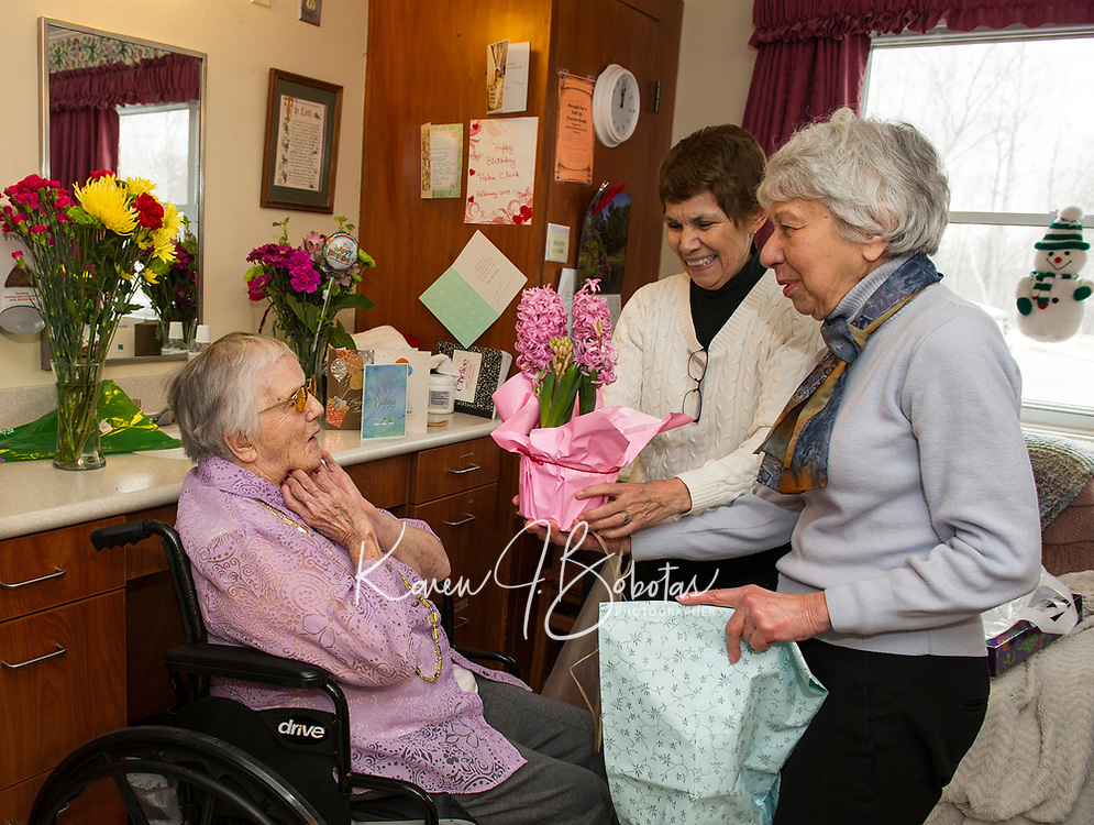 Helen Clark receives pretty pink hyacinths from Liz Clark and Martha Levesque as she celebrates her 100th birthday with family and friends on Sunday afternoon at Genesis Rehab Facility.  (Karen Bobotas/for the Laconia Daily Sun)