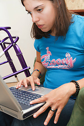 Young woman with Cerebral Palsy, who uses a walking frame, studying on laptop computer.