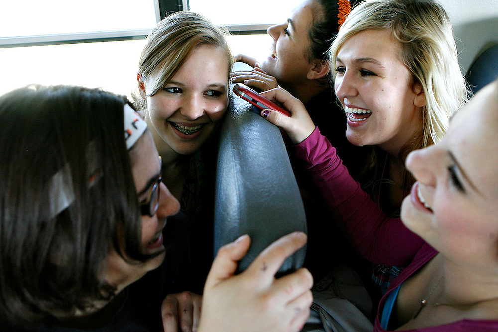 Charlotte Johnson, left, Karissa Shiflet, Ashlen Ayers, Emily Schroeder and Brittany Blackketter laugh while listening to a Youtube clip on a cell phone during a bus ride to Moses Lake for a match. The bus driver forbid the girls from singing on the bus, so they found other ways to entertain themseleves.