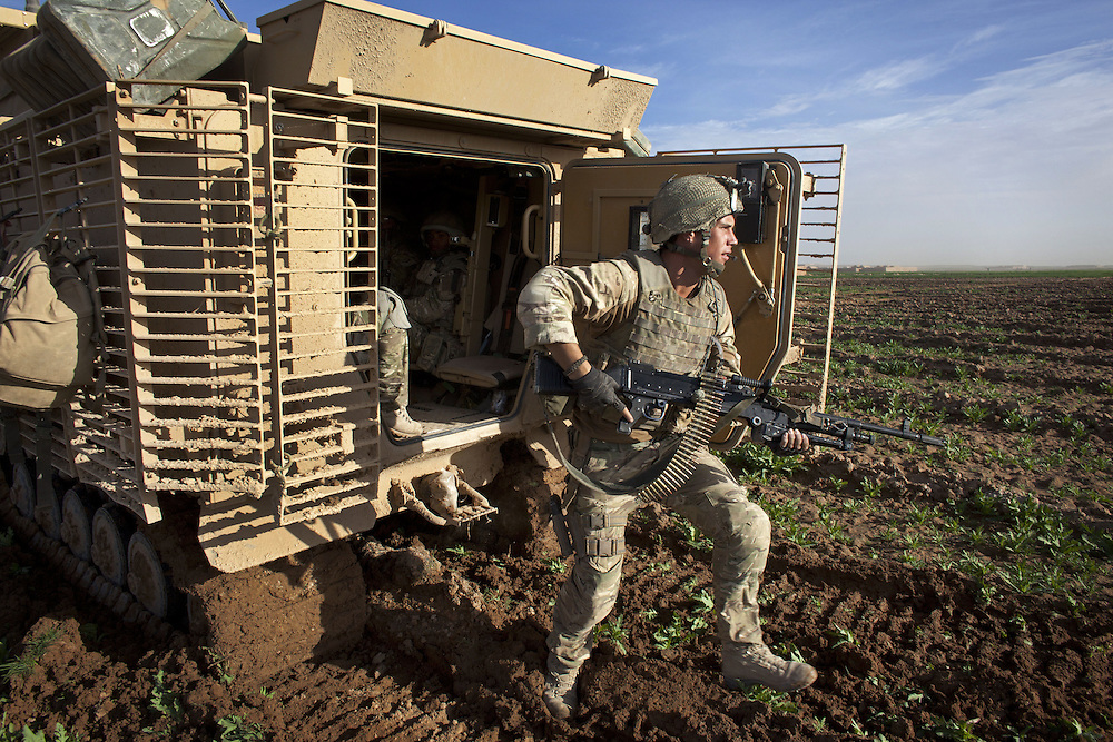 A British soldier of 16 Air Assault Bde's elite BRF (Brigade Reconnaissance Force) dismounts from a Warthog tracked vehicle as the troops move from compound to compound searching for weapons and explosives as part of an operation in the Western Dasht, Helmand Province, Southern Afghanistan on the 18th of March 2011.