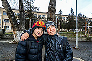 """Felix (r in the picture) a ten-year-old from Shushi, who is attending fifth grade of primary school in Stepanakert asked us if we were from """"Santa Claus country?"""" when I went to visit bombed school number ten in Stepanakert on Wednesday, Dec 23, 2020. I asked why he asked me so, and he said that he wanted a brand new tea shirt from Messi soccer player. He said he likes the new school in Stepanakert but he said that he misses his own school and his classmates in Shushi.<br /> His friend David (L in the picture), won't leave him alone. They walked shoulder to shoulder with one another as they had finished their classes for the day. (Photo/ Vudi Xhymshiti)"""