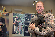 Tom Dokken holds a seven week old Black Lab pup at his Oak Ridge Kennels office in Minneosta