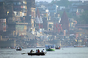 Boats on the Ganges River in Varanasi, India, with the Dasasvamedha Ghat in the background. Colorful and popular Dasasvamedha Ghat gets a lot of attention from religious pilgrims, locals, and tourists alike and is one of the busiest bathing ghats in the city of Varanasi.