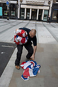 An employee stops to pick up a dropped Union Jack flag from the pavement outside a retailers Bond Street address, on 5th June 2019, in London, England.
