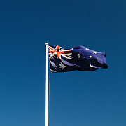 Australian flag flying in the breeze with a clear blue sky in the background