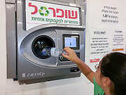Bottle recycling. Young girl recycles bottles in an automatic machine. Photographed in Israel