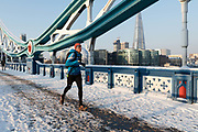 A jogger runs across a snow covered Tower Bridge in London, England on February 28th, 2018. Freezing weather conditions dubbed the Beast from the East have brought snow and sub-zero temperatures to the UK.