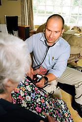 Nurse practioner taking blood pressure of an elderly patient in her own home; West Yorkshire UK
