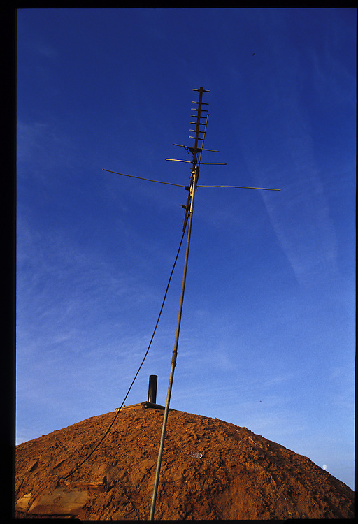The home of Eugene Chee Sr. in Oljeto is equipped with a television antenna.  A cord strung from a generator behind a nearby house provides electricity.