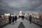 View of tourists and local people crossing the Millennium Bridge with St Pauls Cathedral rising in the background in London, United Kingdom. Londoners nicknamed the bridge the Wobbly Bridge after people felt an unexpected swaying motion on the first two days after the bridge opened. The bridge was closed later that day, and was closed for almost two years while modifications were made to eliminate the sway entirely.
