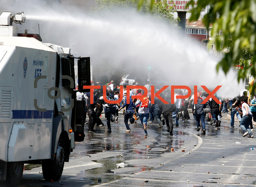Protestors clash with Turkish riot police during the May Day rally in Istanbul, Turkey 01 May 2013. Turkish police and protesters clashed in central Istanbul on 01 May after authorities moved to prohibit traditional Labour Day rallies at Taksim Square. Police used water cannons and tear gas against the demonstrators near Taksim Square. Witnesses reported clashes in several neighbourhoods in the area. May 1 demonstrations in Istanbul organized demonstrators clashed with police in protest against the government. Events, many demonstrators were injured, a large number of people affected by the tear gas used by police. Photo by AYKUT AKICI/TURKPIX