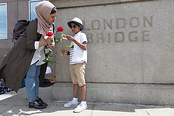 """© Licensed to London News Pictures. 11/06/2017. LONDON, UK.  A woman and a boy (permission for photograph given) with red roses on London Bridge this afternoon. 1,000 red roses with messages of """"love and solidarity"""" were given to passers by on London Bridge today.  Photo credit: Vickie Flores/LNP"""