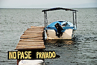 A lone panga sits at the end of a private pier in the shallows of Lake Nicaragua near Granada.